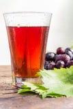 葡萄汁和一串葡萄与绿色叶子的 库存照片