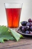 葡萄汁和一串葡萄与绿色叶子的 免版税库存照片