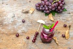 葡萄汁顶视图在玻璃瓶子的在老木头 库存图片