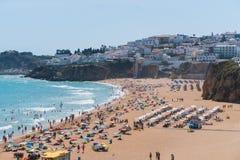 葡萄牙阿尔加威老镇albufeira和含沙城市海滩人民在海附近晒日光浴并且休息 新的成人 库存图片