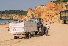 葡萄牙- 2017年4月:在海滩的垃圾收集工在2017年4月17日,位于波尔蒂芒,葡萄牙 普腊亚da Rocha 免版税库存图片