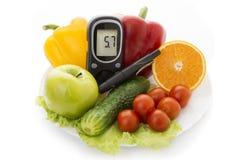葡萄糖水平和健康有机食品的Glucometer 库存照片