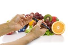 葡萄糖水平和健康有机食品的Glucometer 免版税库存图片