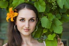 葡萄背景的年轻美丽的妇女  免版税库存照片