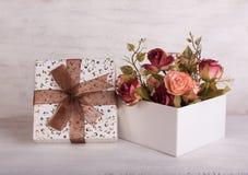 葡萄酒上升了花束和礼物盒在难看的东西木头背景 库存照片