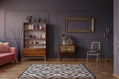 葡萄酒与一个被仿造的地毯的客厅内部,碗柜, gol 免版税库存图片