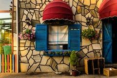 葡萄酒与五颜六色的快门和伞的餐馆窗口 库存图片