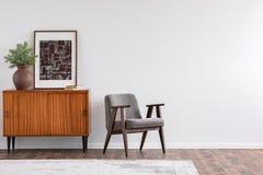 葡萄酒与减速火箭的家具和海报,与拷贝空间的真正的照片的客厅内部在白色墙壁上 免版税库存图片