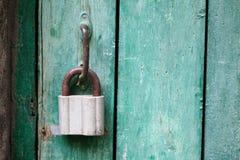 葡萄酒与垂悬的锁,闭合的绿色木门的门把手 在树干的绿色和黄色叶子 免版税库存图片