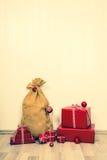 葡萄酒与大袋的圣诞节背景圣诞老人和红色礼物 库存照片