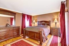 葡萄酒与木家具、红色帷幕和地毯的卧室内部 免版税库存照片