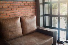 葡萄酒与棕色沙发的客厅内部 免版税库存图片