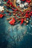 葡萄酒与红色冬天莓果、假日装饰和曲奇饼花圈的圣诞节背景  免版税库存照片