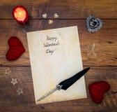 葡萄酒与红色拥抱心脏的情人节卡片、木装饰、红色蜡烛和墨水和纤管在葡萄酒橡木-顶视图 库存图片