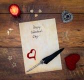 葡萄酒与红色拥抱心脏的情人节卡片、木装饰、被绘的牡鹿、红色蜡烛和墨水和纤管在葡萄酒橡木 图库摄影