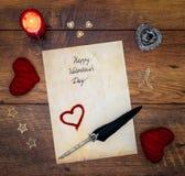 葡萄酒与红色拥抱心脏的情人节卡片、被绘的牡鹿、红色蜡烛和墨水和纤管在葡萄酒橡木-顶视图 库存图片