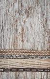 葡萄酒与绳索的难看的东西在木纹理的背景和链子 免版税库存照片