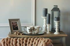 葡萄酒与蜡烛的沙发桌,在斯堪的纳维亚人的被编织的毯子 库存图片