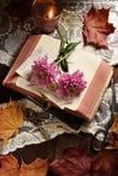 葡萄酒与被打开的书和花的样式静物画 库存图片
