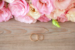 葡萄酒与金戒指和美丽的花的婚礼背景 免版税库存图片