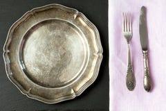 葡萄酒与银器的金属盘在板岩背景 餐位餐具表 免版税库存照片