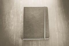 葡萄酒乌贼属颜色:有小条的老精装书笔记本在木头 库存图片