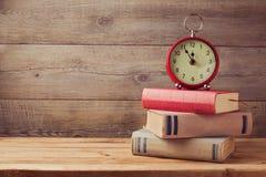 葡萄酒书和时钟在木桌上与拷贝空间 免版税库存照片