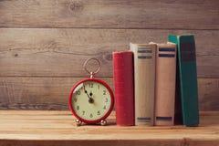 葡萄酒书和时钟在木桌上 免版税库存图片