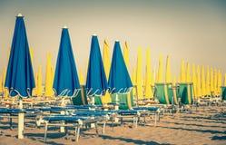 葡萄酒伞和sunbeds在里米尼使意大利靠岸 免版税库存照片