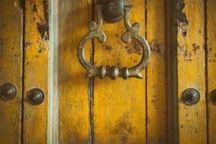 葡萄酒减速火箭的样式黄色木头门 老铜门把手 Abstra 免版税库存照片