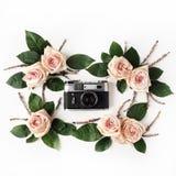 葡萄酒减速火箭的照片照相机、米黄玫瑰和绿色叶子 免版税图库摄影