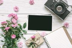 葡萄酒减速火箭的照相机和桃红色玫瑰开花与空白的照片框架、被排行的笔记本和礼物盒的花束 免版税库存照片
