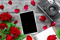 葡萄酒减速火箭的照相机和空白的照片框架与红色玫瑰开花花束和被排行的笔记本 库存图片