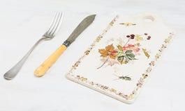 葡萄酒刀子在一个木板的一把叉子 库存照片