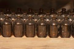 葡萄酒医学瓶由棕色玻璃复盖制成与尘土,在木架子 免版税库存图片