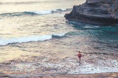 葡萄酒口气,有站立在海滩的冲浪板的一个人在巴厘岛 库存图片