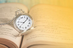 葡萄酒口袋时钟和书 免版税库存照片