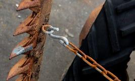 葡萄酒古色古香的汽车拖拉机轮子和显示铁锈的切削刀贯彻和链子 库存照片