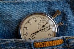 葡萄酒古董秒表,在有橙色条纹口袋的老被穿的深蓝牛仔裤,价值措施时间,老时钟箭头分钟,秒 免版税库存图片