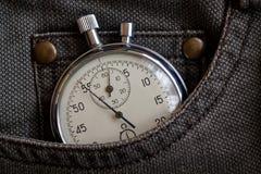 葡萄酒古董秒表,在破旧的棕色牛仔裤装在口袋里,价值措施时间,老时钟箭头分钟,第二个准确性定时器纪录 库存照片