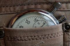 葡萄酒古董秒表,在破旧的米黄牛仔裤装在口袋里,价值措施时间,老时钟箭头分钟,第二个准确性定时器纪录 免版税图库摄影