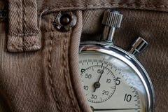 葡萄酒古董秒表,在米黄牛仔布口袋,价值措施时间,老时钟箭头分钟,第二个准确性定时器纪录 免版税库存照片