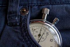 葡萄酒古董秒表,在老蓝色牛仔裤装在口袋里,价值措施时间,老时钟箭头分钟,第二个准确性定时器纪录 图库摄影