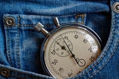 葡萄酒古董秒表,在老被佩带的深蓝牛仔布口袋,价值措施时间,老时钟箭头分钟,第二个准确性定时器 图库摄影