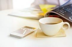葡萄酒和淡色定调子在咖啡店的咖啡杯和商人样式有手机的 库存照片