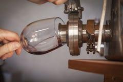 葡萄酒商人倾吐酒口味从桶的入玻璃 免版税库存图片