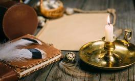 葡萄酒嘲笑 有灼烧的蜡烛的特写镜头烛台怂恿,文本的黄色纸在土气木委员会 图库摄影