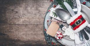 葡萄酒圣诞晚餐桌与板材、利器、冷杉分支、空白的标记的嘲笑和雪人的餐位餐具在土气木 库存图片
