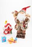 葡萄酒圣诞老人玩偶、装饰小屋和礼物盒 免版税图库摄影