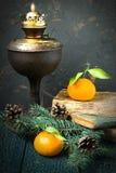 葡萄酒圣诞节大气:煤油灯,书,蜜桔 库存照片